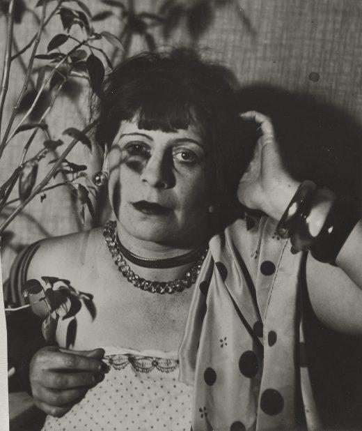 Florence Henri mit getupftem Schal und Blumen